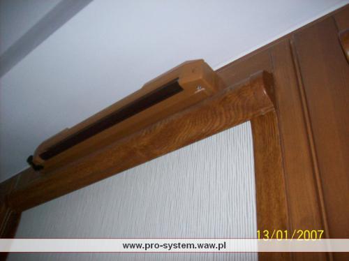 Tkanina typu Stickan w rolecie na oknie. Kaseta z prowadnicami drewnopodobnymi.